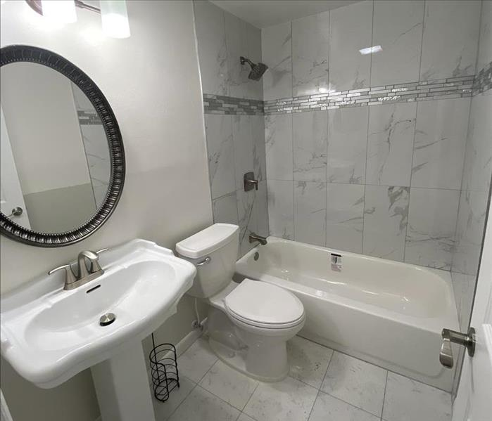 white bathroom with sink, toilet, and shower